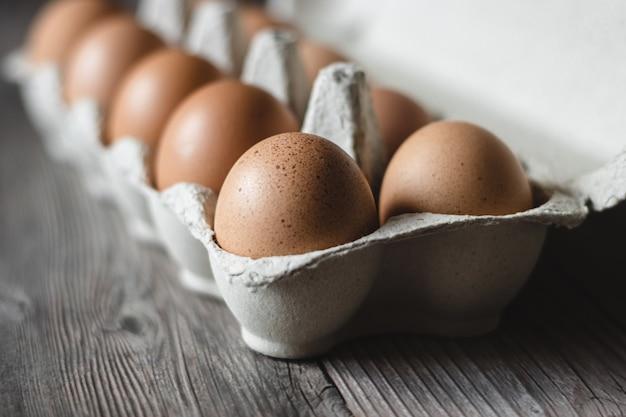 나무 표면에 판지에 갈색 닭고기 달걀.