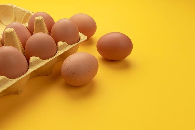Коричневые куриные яйца в картонной коробке на желтом фоне