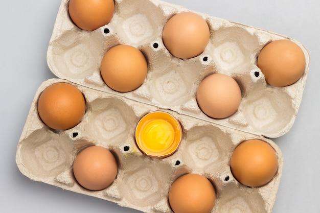 판지 용기에 갈색 닭고기 달걀. 용기에 깨진 달걀 하나. 플랫 레이