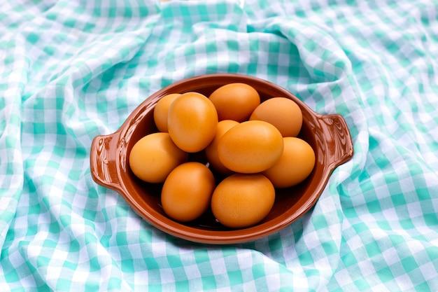 파란색과 흰색 직물에 접시에 갈색 닭고기 달걀