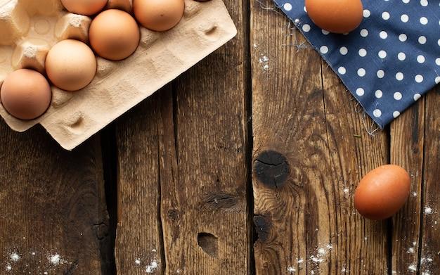 木製の背景にパッケージされた茶色の鶏の卵