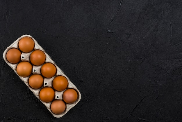 Brown chicken eggs in rack on black table