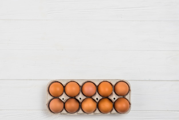 Brown chicken eggs in rack on white table