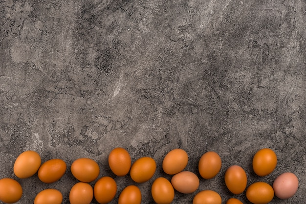 Brown chicken eggs scattered on grey table