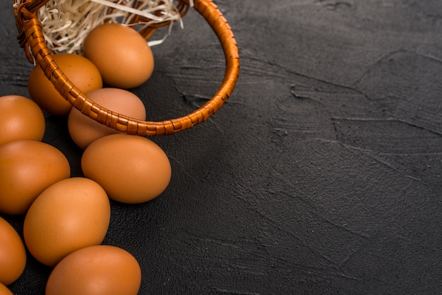 Brown chicken eggs with basket on table