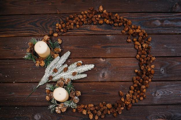 Коричневый новогодний фон в виде круга украшен праздничным новогодним декором и аксессуарами, гирляндой. праздничная новогодняя открытка.