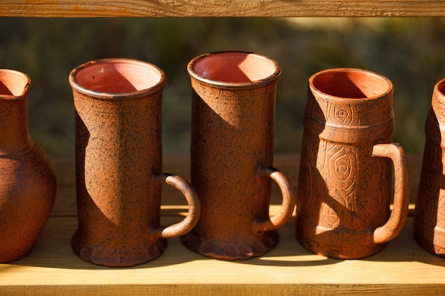 茶色の粘土のマグカップが木製の棚に並んでいます。