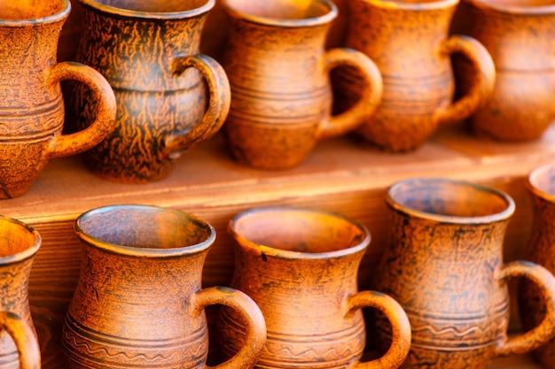 Горшки из коричневой глины стоят рядами. ручной работы