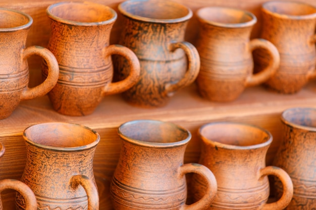 Brown clay pots are in rows. handmade