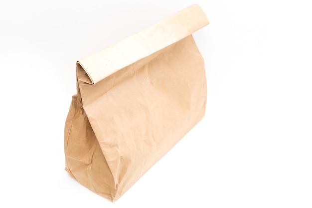 흰색 배경에 격리된 테이크아웃을 위한 갈색 투명 빈 공예 종이 가방. 포장 템플릿을 조롱합니다. 배달 서비스 개념입니다. 공간을 복사합니다.