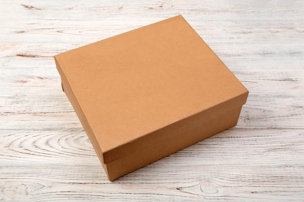 木製の背景に茶色の閉じた段ボール箱。あなたの設計のための空白の平面図