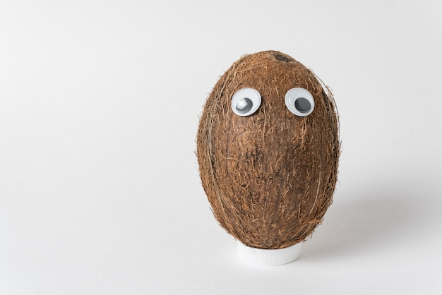 Brown coconut with googly eyes on white wall. nut character with funny face