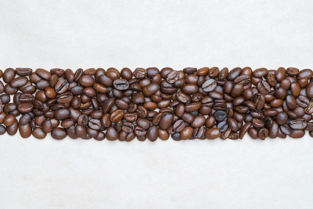 Brown coffee beans on background of light texture recycled eco-friendly paper. central horizontal location objects, copy space for text at top and bottom. flat lay, close-up view of still life.
