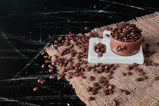 Brown coffee beans in a cup.