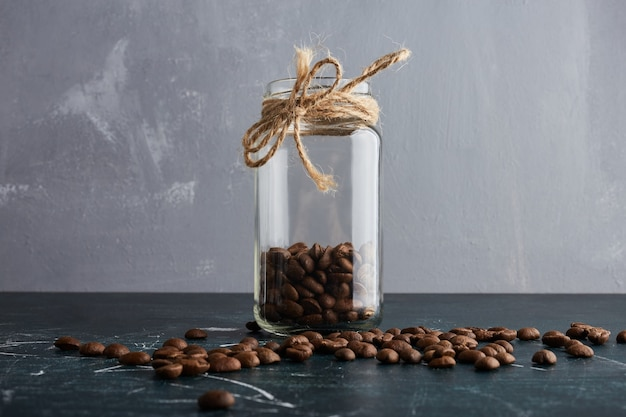 Brown coffee beans in a glass jar.