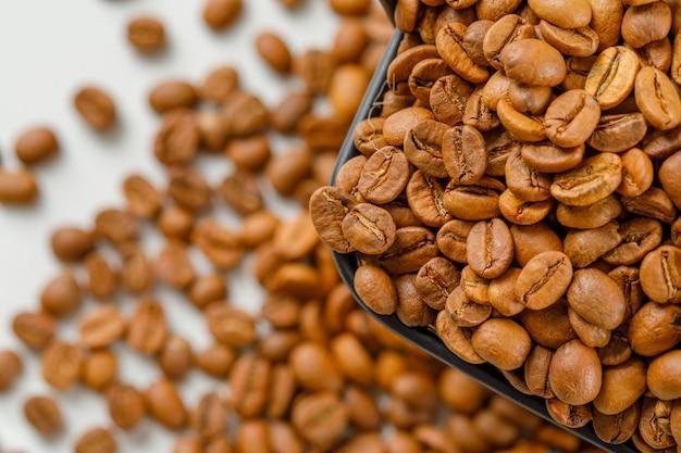 흩어져 콩에 검은 바구니에 갈색 커피 콩. 높은 각도보기.