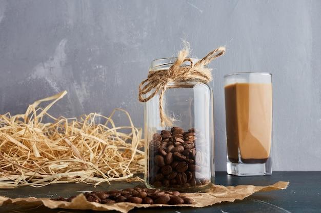 Коричневые кофейные зерна в стеклянной банке.