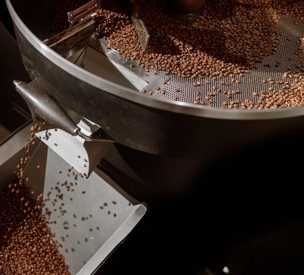 Коричневые кофейные зерна в охлаждающем лотке машины для обжарки кофе