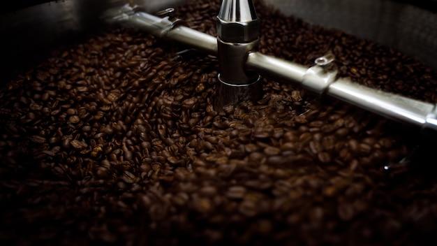 로스팅 스핀 머신에 있는 갈색 커피 콩은 스포츠 초점과 긴 노출 샷을 닫습니다