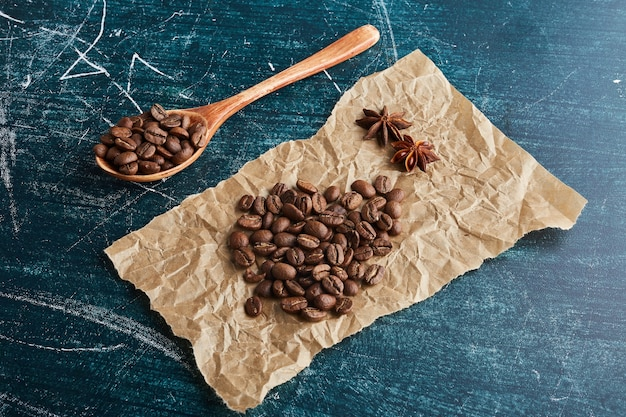 Коричневые кофейные зерна на листе бумаги.