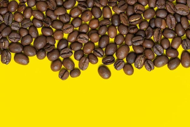 明るい黄色の背景に茶色のコーヒー豆。上部の水平位置オブジェクト、下部のテキスト用のスペースをコピーします。カラフルなコーヒーの静物のフラットレイ、クローズアップビュー。