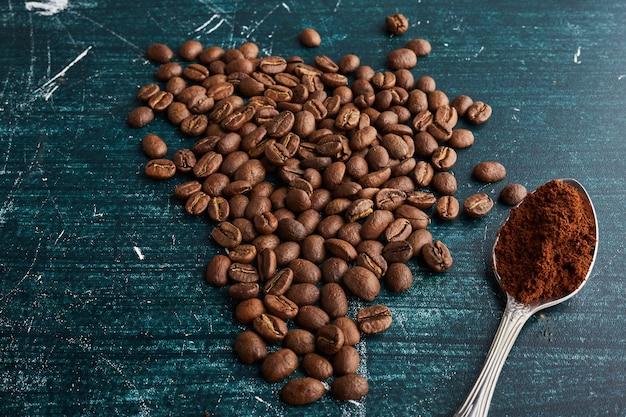 Коричневые кофейные зерна с ложкой порошка.