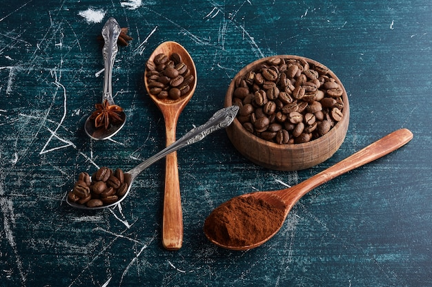 Brown coffee beans in wooden cup and spoons.