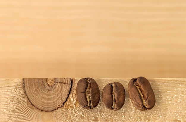 Brown coffee beans on yellow textured wooden board background close up.