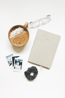 Brown coffee cup on white background with photos and eyeglasses