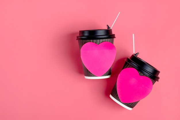 Brown coffee cups, red heart-shaped sticker on pink background. happy valentine's day flat lay