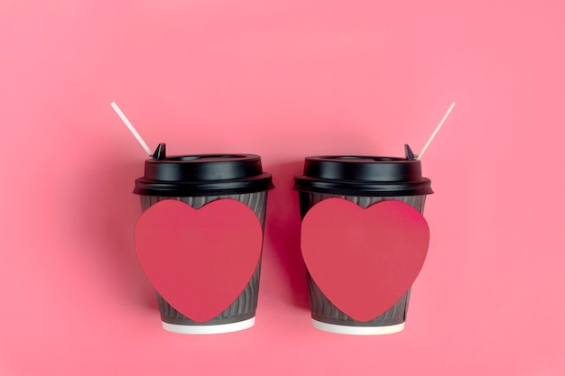 Brown coffee cups, red heart-shaped sticker on pink background. love is. concept for coffee lovers, love is. happy valentine's day flat lay