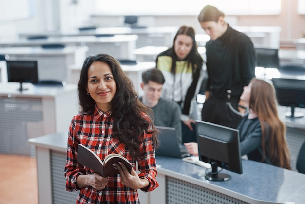 手で茶色の色の本。近代的なオフィスで働くカジュアルな服装の若い人たちのグループ