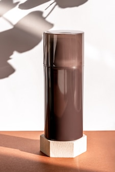 Brown cosmetic shower gel bottle on wooden geometric pedestal podium, product packaging with natural shadows from plants, antiperspirant for men, shaving foam, shampoo mockup. front view
