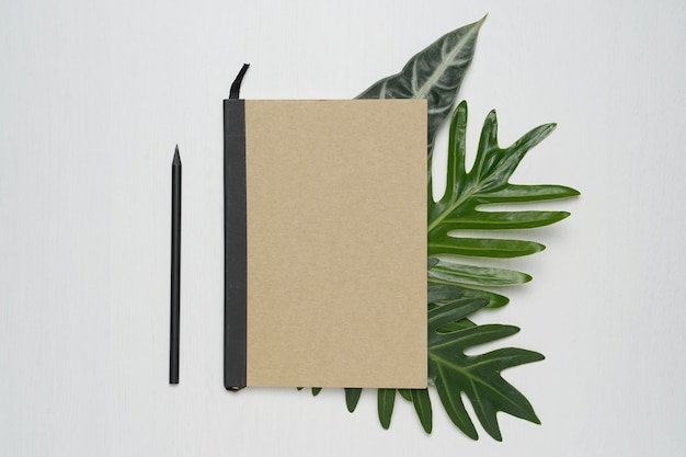 Brown cover notebook on white wooden background with tropical monstera leaves