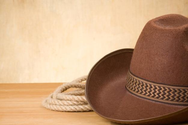 Коричневая ковбойская шляпа и веревка на фоне текстуры древесины