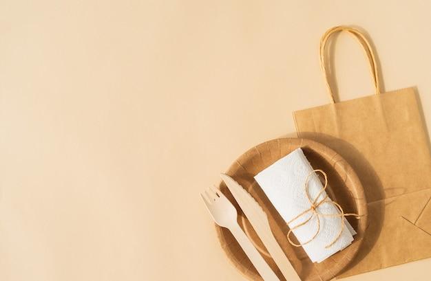 Одноразовая сумка коричневого цвета и чашка для посуды, тарелка и деревянная вилка, нож на коричневой поверхности, плоский вид сверху