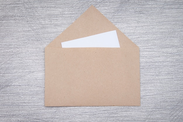 Brown craft envelope with white paper card on grey background.