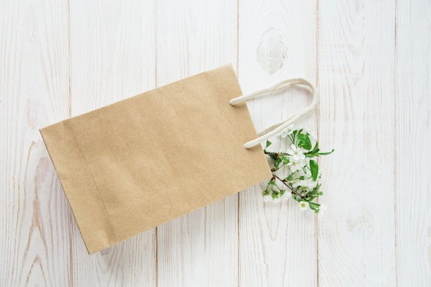 Brown craft paper bag with handles.white background.fresh flowers.flat lay.