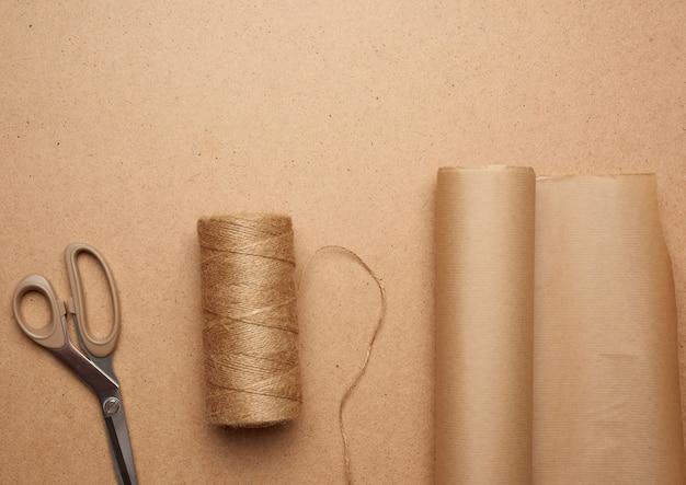 茶色のクラフト紙ロール、糸のかせ、はさみ