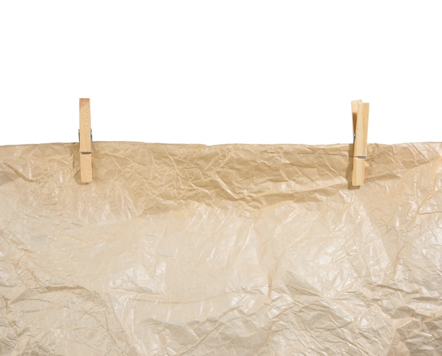Brown crumpled paper hanging on wooden clothespins, texture isolated on white surface