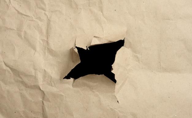 茶色のしわくちゃの紙に穴があり、端が破れて湾曲しています。抽象的な表面