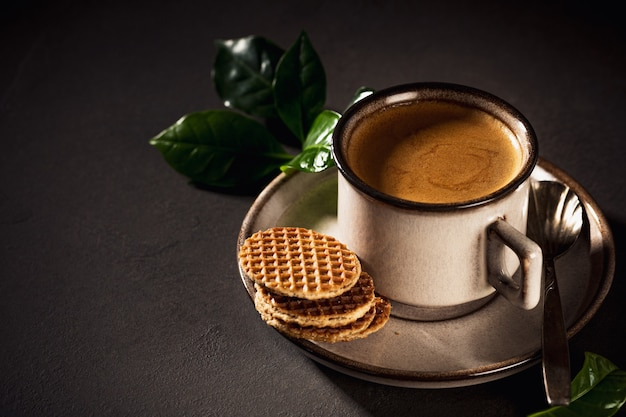 Brown cup of coffee and dutch traditional stroopwafels. food surface with copy space