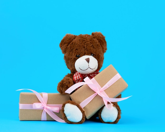 Brown cute teddy bear and gifts wrapped in brown eco kraft paper and tied with a ribbon