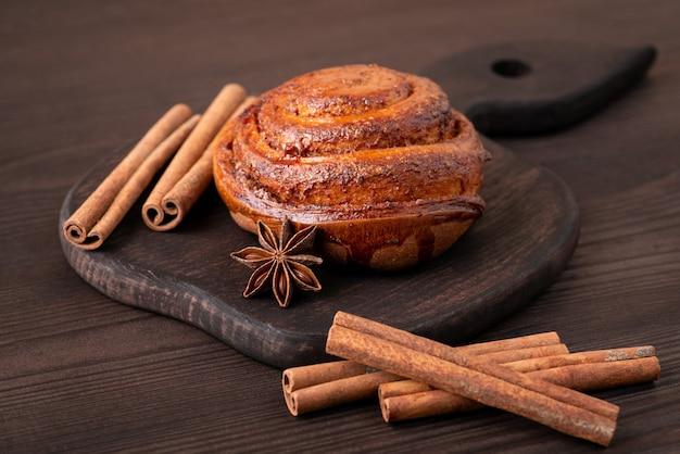 Коричневая разделочная доска на темном деревянном столе, сладкие булочки, палочки корицы и звездочка аниса на ней
