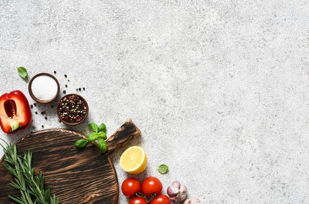 Коричневая разделочная доска со специями и овощами на свету, конкретном кухонном столе.