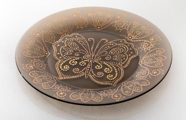 Коричневая декоративная тарелка на белом фоне с геометрическим узором