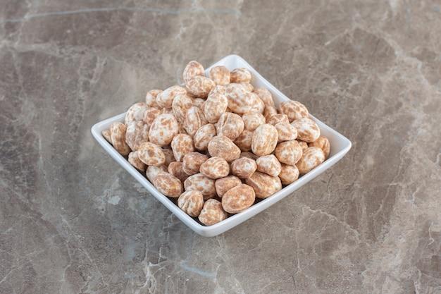 Caramelle deliziose marroni sul piatto bianco sulla superficie grigia.