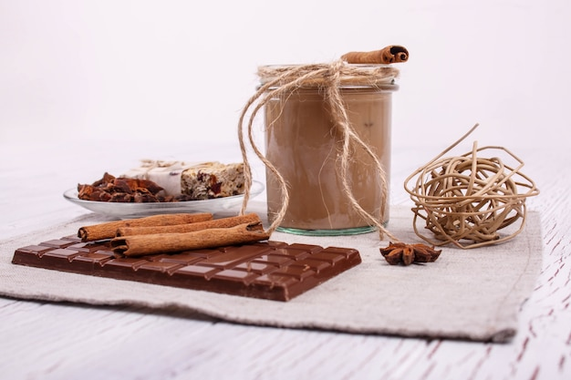 Brown detox coctail with cinnamon sticks and chocolate lie on the table