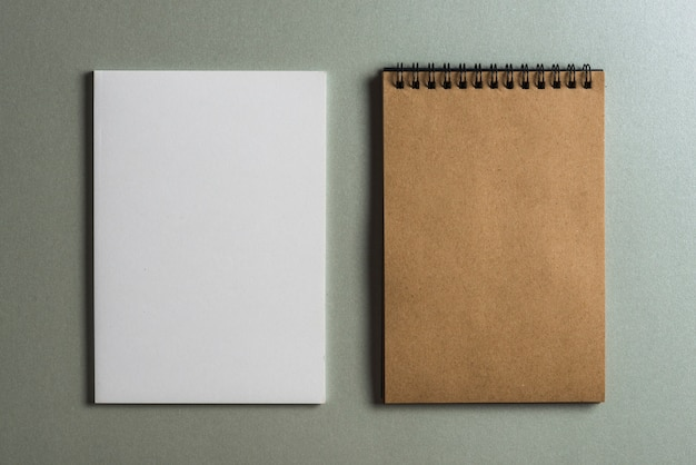 Brown diary and blank white page against colored background