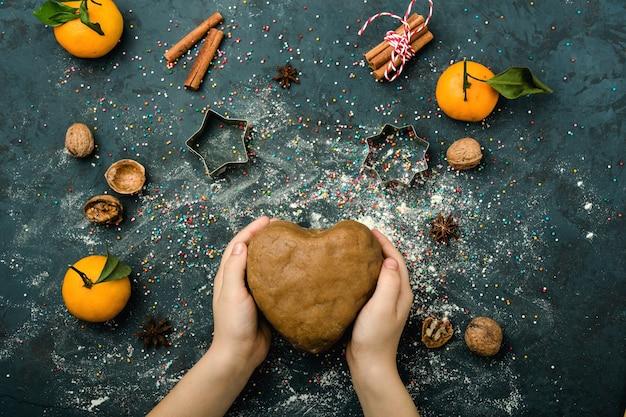 ハートの形をした茶色の生地、子供の手、小麦粉のほこり、星の形、クルミ、葉のあるみかん、上面図、紺色の背景。休日のコンテンツ